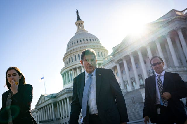 <p>West Virginia Democratic Senator Joe Manchin, centre, leaves the US Capitol following a vote on 27 October, 2021</p>
