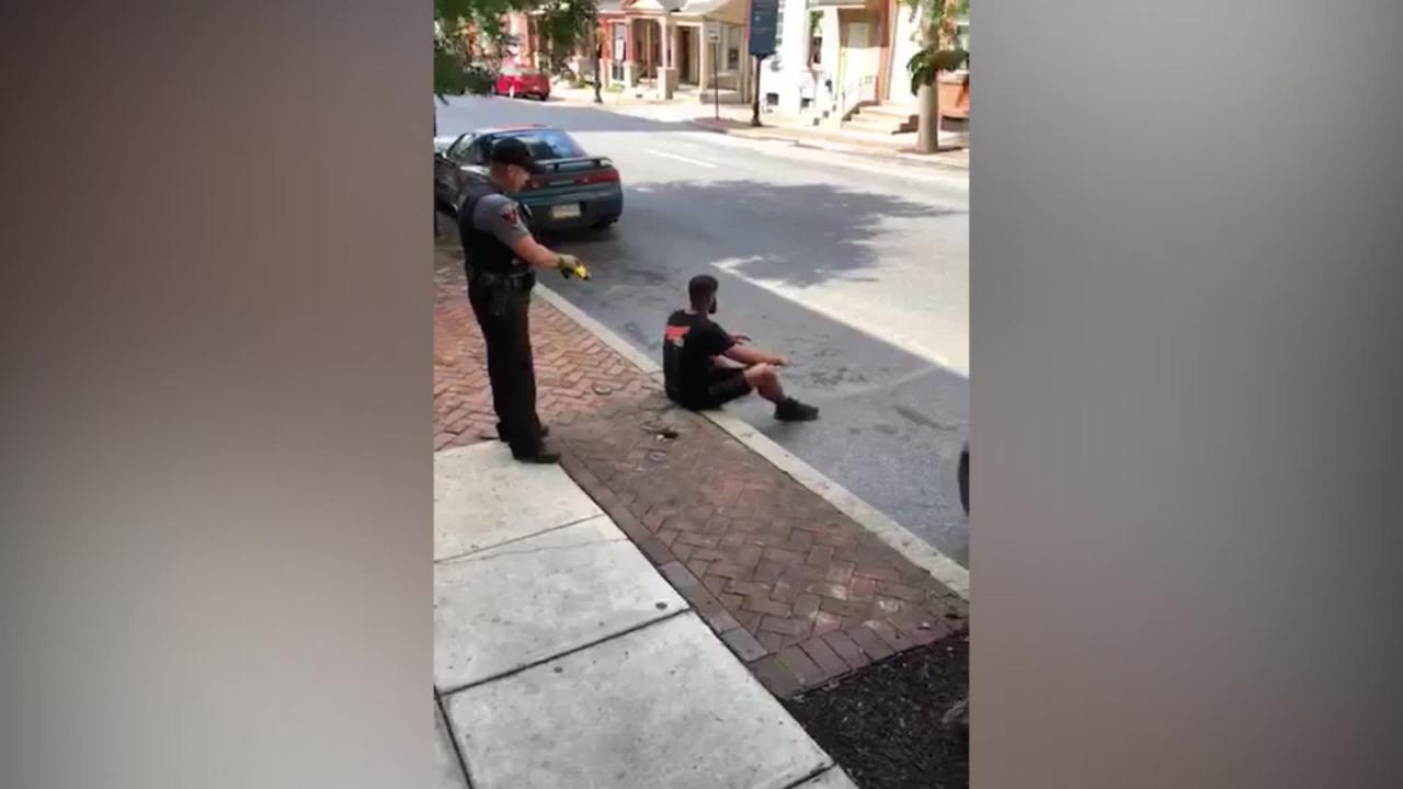 Unarmed black man tased by police in the back while sitting on a curb