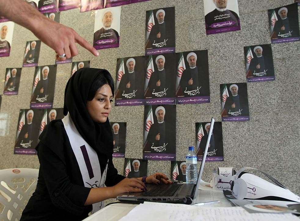 A woman works on her laptop in one of Hassan Rouhani's campaign offices in Tehran