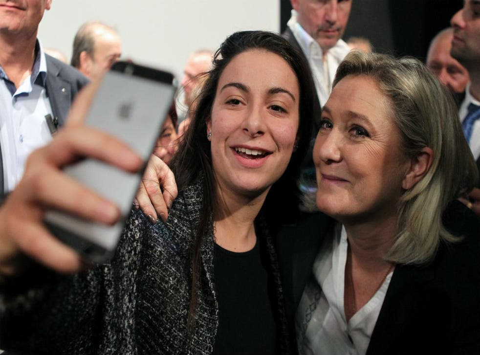 From left to right - out of focus iPhone, far-right supporter, far-right politician