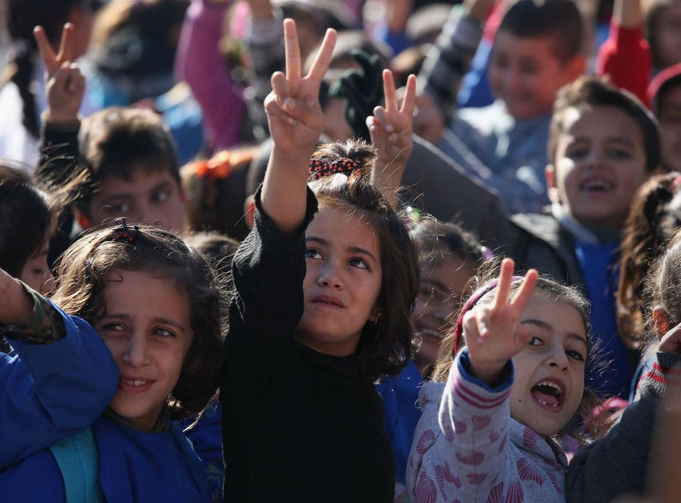 Children flash the victory sign after singing the Rojava anthem at a public elementary school on November 12, 2015 in Qamishli, Rojava, Syria