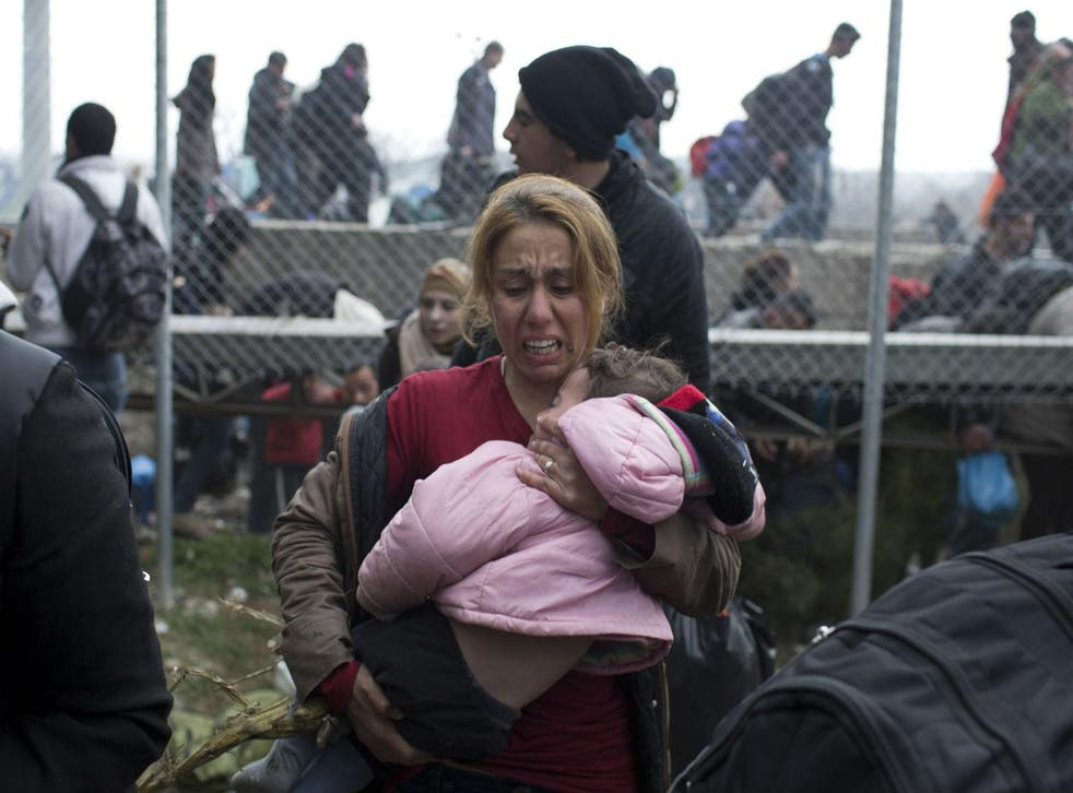 A woman holds her child as she runs away from police firing tear gas on the Greek-Macedonian border, 29th Febraury 2016.  Picture: Petros Giannakouris/AP