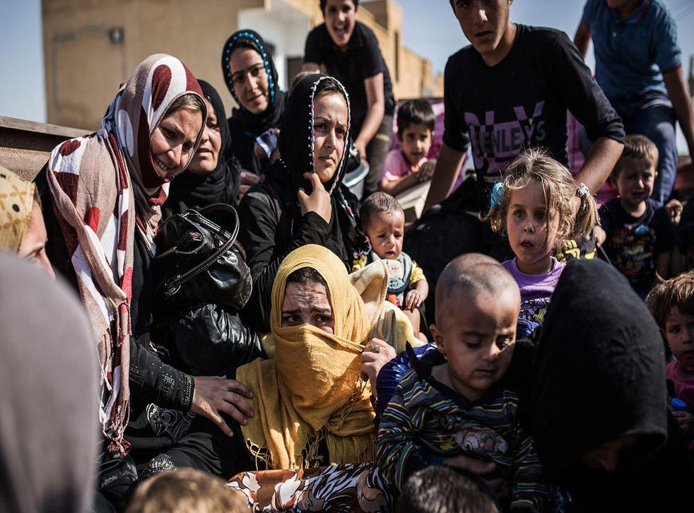 Syrian refugees cross the Syria-Turkey border on 22 June 2015, as they return to the northern Syrian town of Tal Abyad
