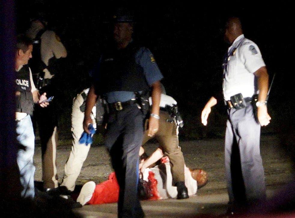 A man lies on the ground with blood on his shirt after a police officer involved shooting in Ferguson, Missouri on August 9th 2015.
