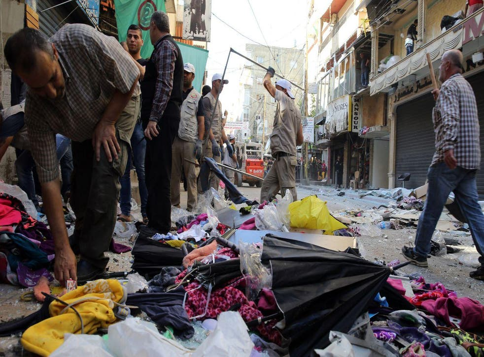 Lebanese municipality workers clear debris from the site of a twin bombing attack in Beirut's southern suburb on 13 November 2015