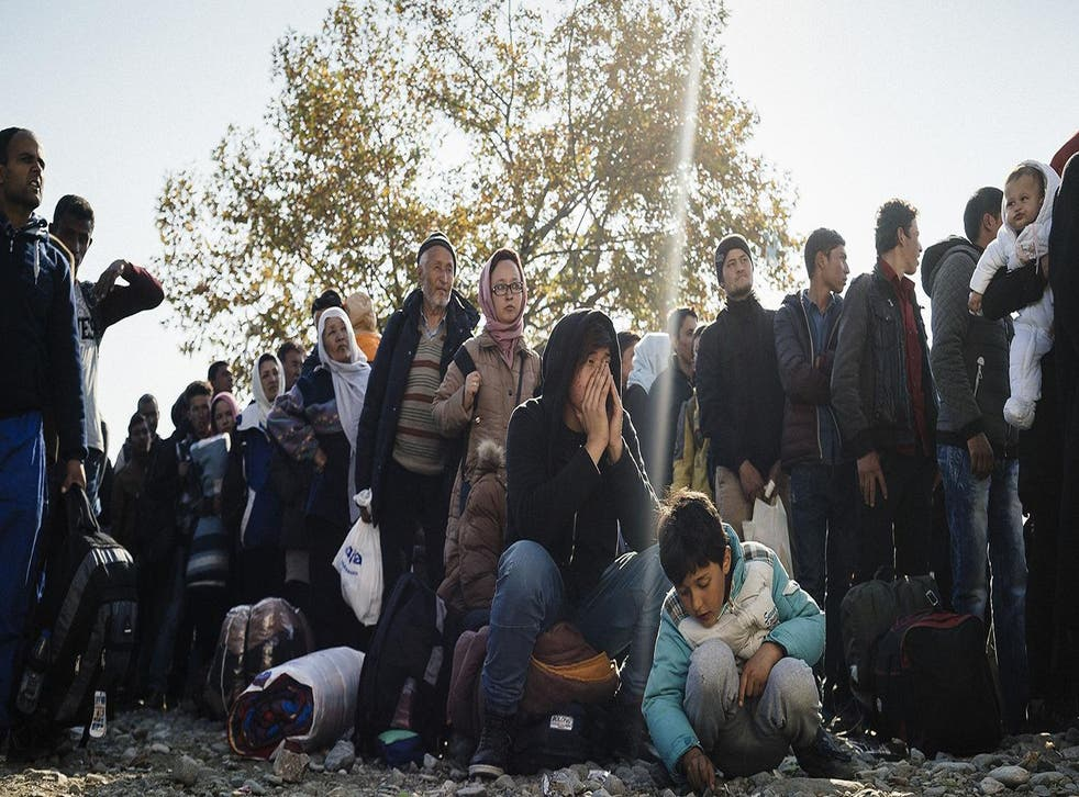Refugees wait to enter a registration camp after crossing the Greek-Macedonian border