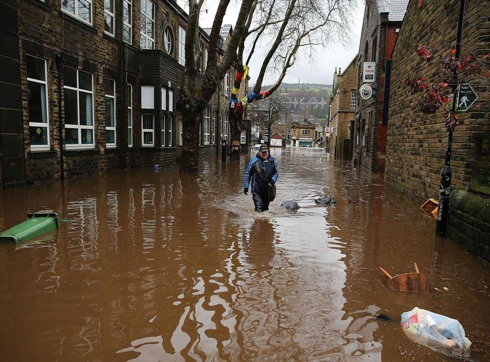 A man wades through floodwaters in Hebden Bridge, Yorkshire