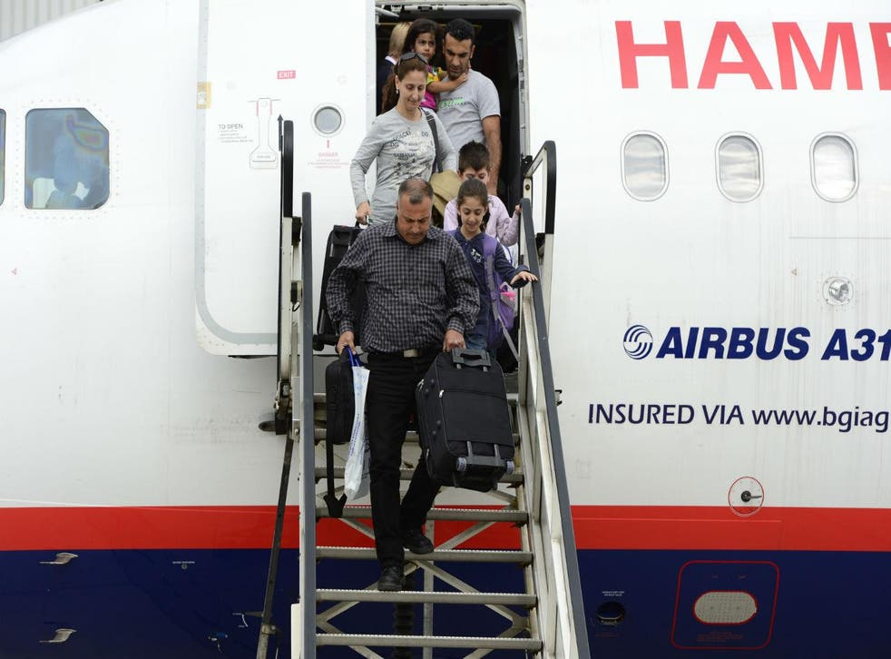 Syrian refugees leave an airplane on the airport in Hanover, central Germany on September 11, 2013