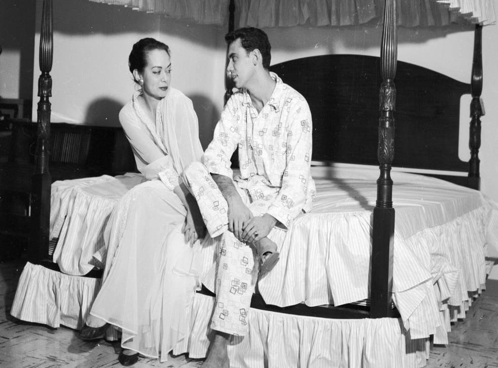 A couple sitting on a specially designed four poster bed, c. 1956