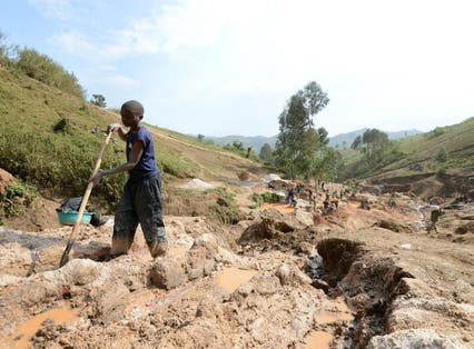 A child separates mineral from rock and sand at a mine in DR Congo