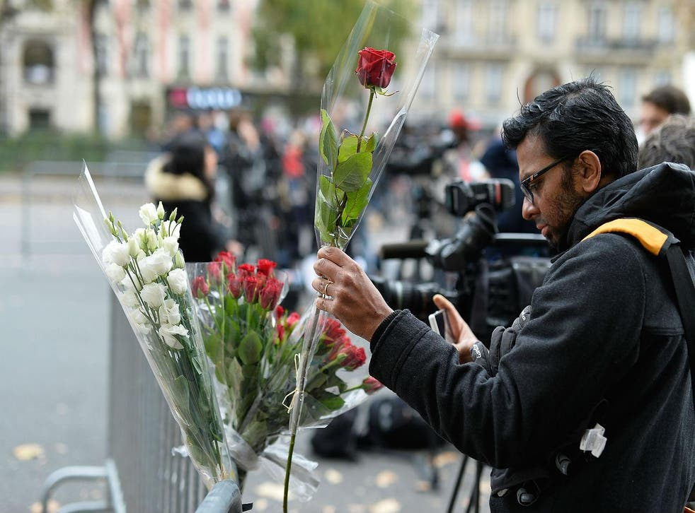 A man places a floral tribute near the Bataclan Theatre on November 14, 2015 in Paris, France