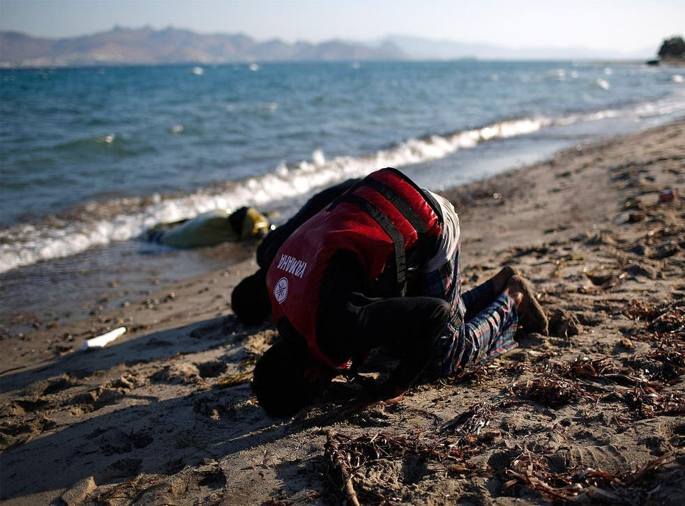 Two people from Pakistan pray on the beach after arriving in Kos, Greece on 29 August 2015