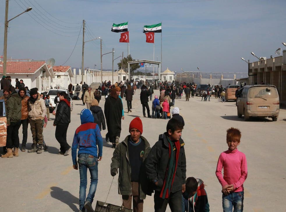 Syrians fleeing Aleppo wait at the crossing on the border between Syria and Turkey, on 5 February 2016