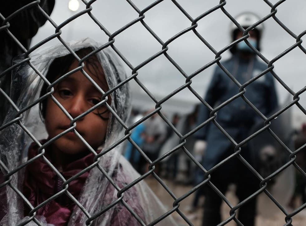 A child waits with her father at the migrant processing center at the increasingly overwhelmed Moria camp on the island of Lesbos
