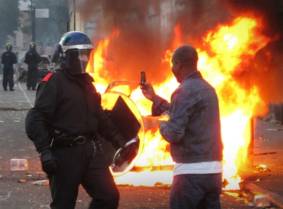 A resident films a police officer on his mobile phone during disturbances in Hackney, London on August 8, 201