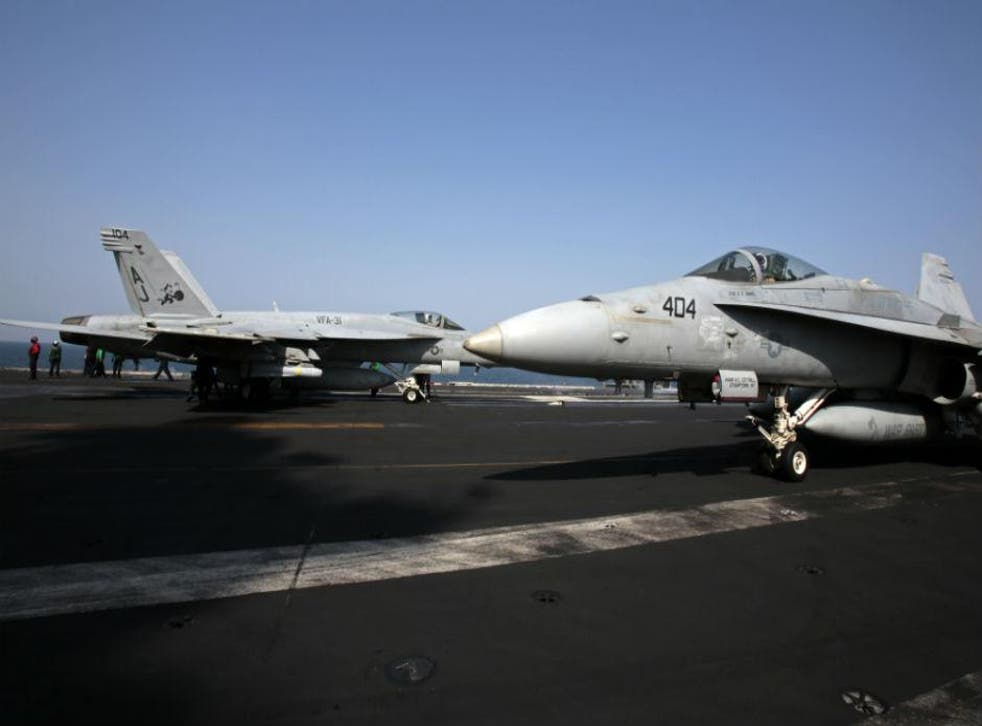 Two FA-18 fighter jets prepare to take-off for Iraq from the USS George HW Bush