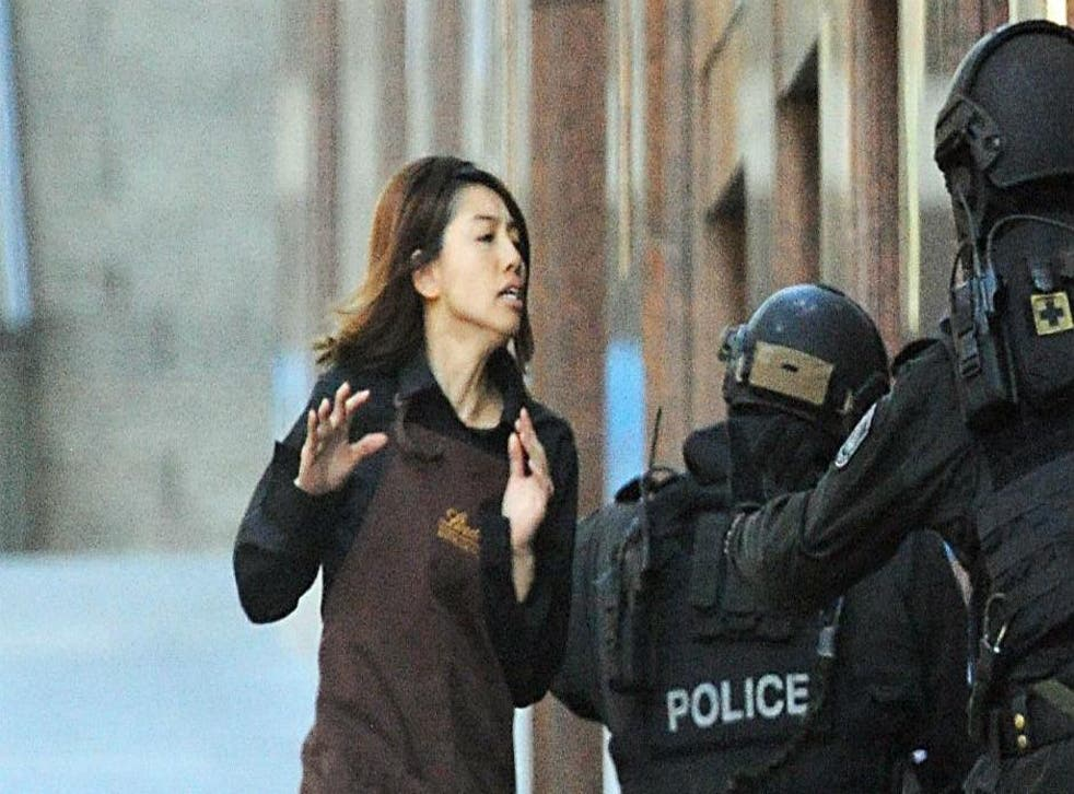 An employee from the Lindt cafe runs towards armed police in central Sydney