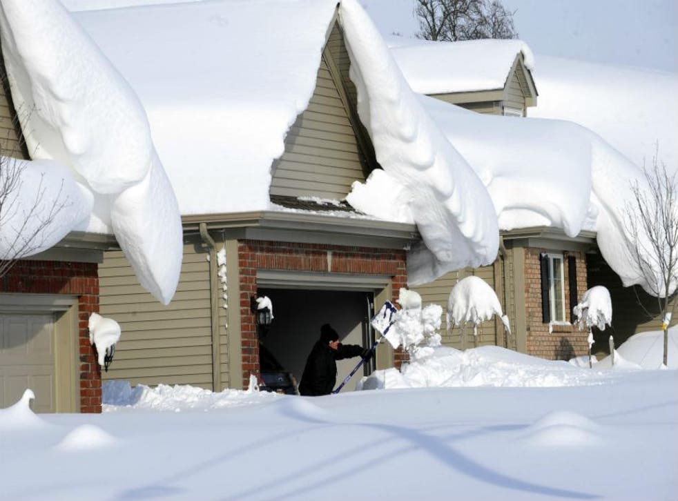 A man attempts to clear snow from his driveway in Lancaster, NY