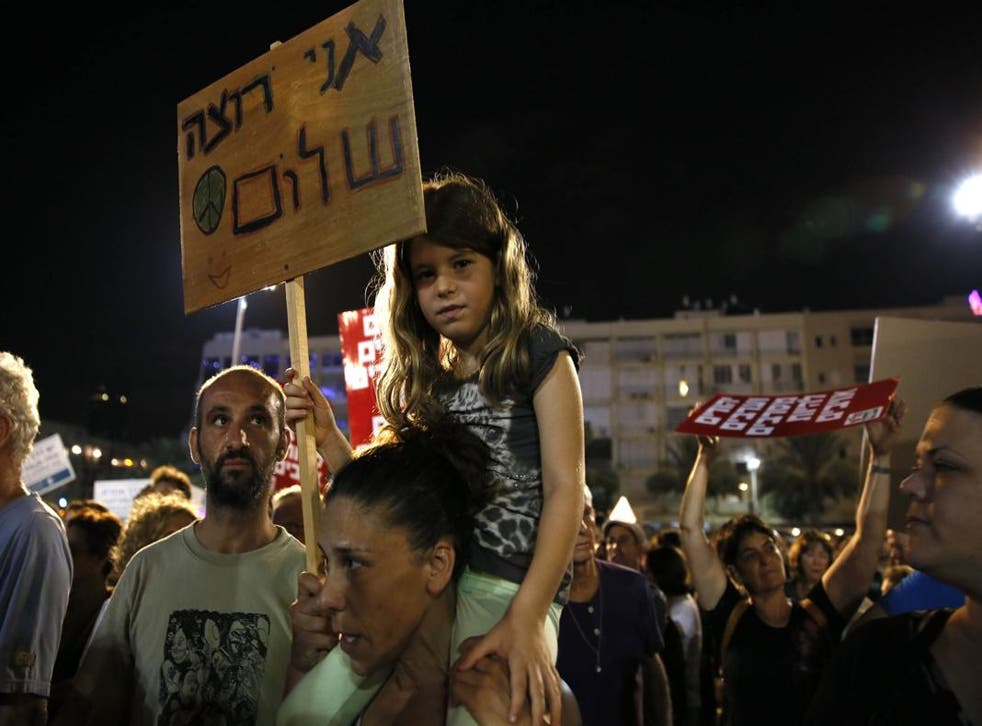 A young girl holds a placard reading in Hebrew: 'I want peace'