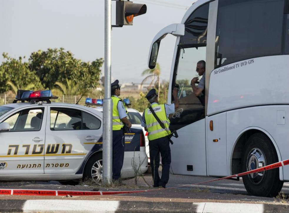 Israeli police officers speak to a bus driver at a checkpoint to the city of Qalansuwa