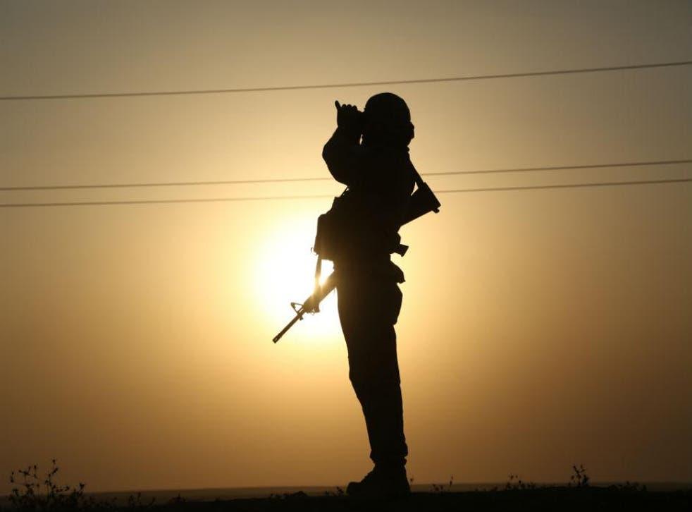 A member of the Kurdish Peshmerga looks for Isis activity through binoculars in northern Iraq