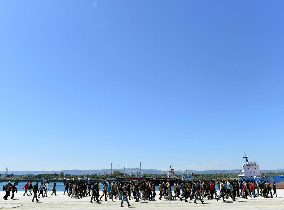 Migrants disembark an Italian naval ship in the Sicilian port of Augusta on 22 April