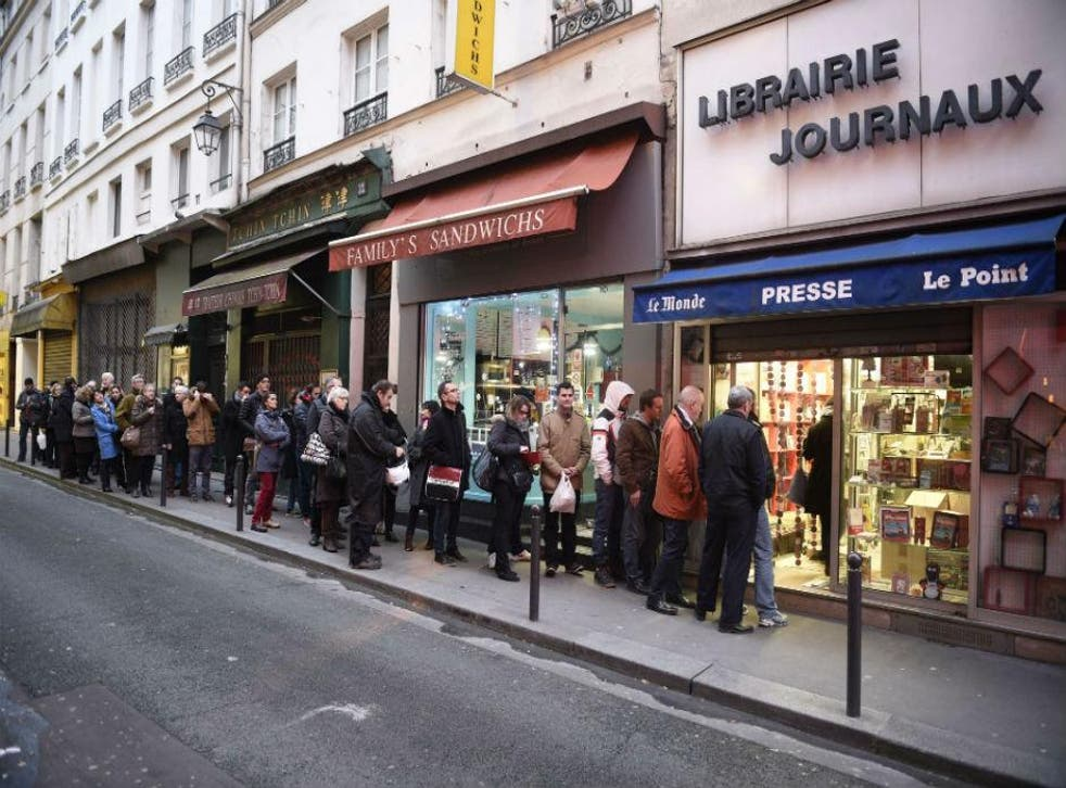 People wait outside a newsagents in Paris on Wednesday morning