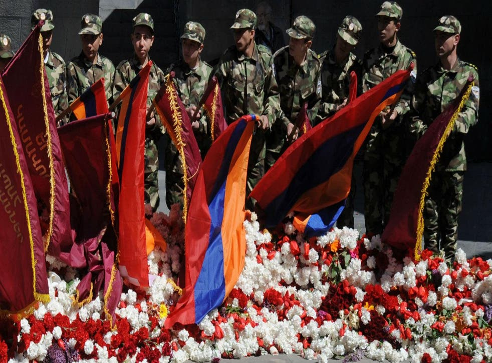 Wearing army-style camouflage costumes young Armenians lower flags as they visit the genocide memorial in Yerevan, 2013