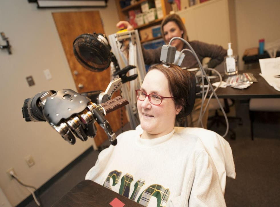 Jan Scheuermann, who has quadriplegia, brings a chocolate bar to her mouth using a robot arm she is guiding with her thoughts