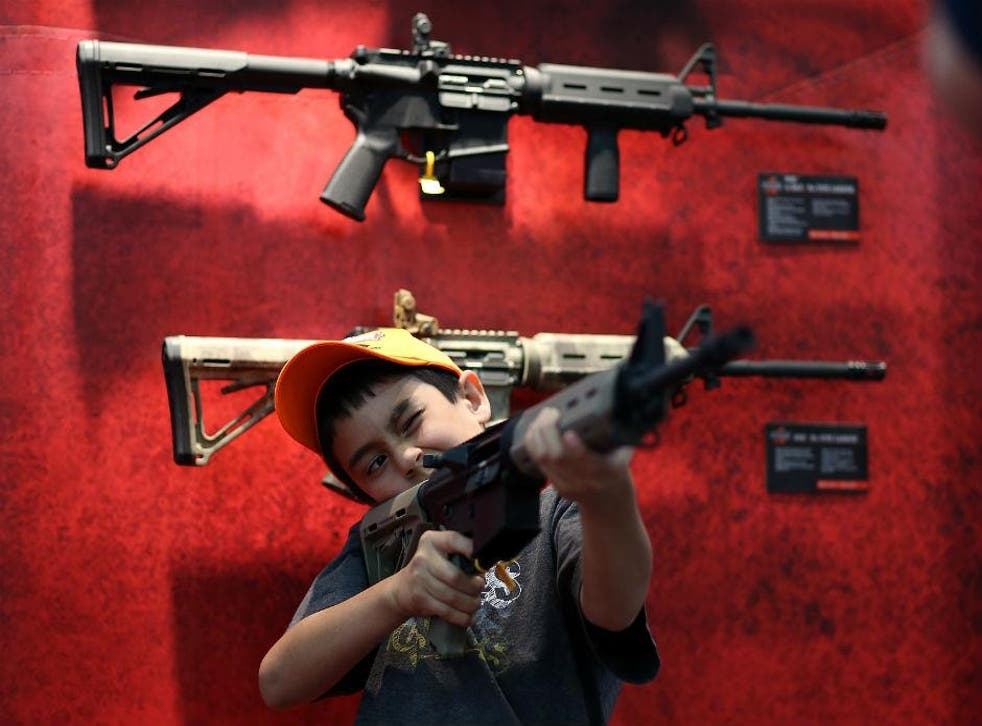A young attendee inspects an assault rifle during the 2013 NRA Annual Meeting