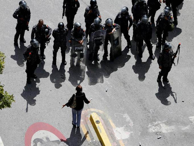 A woman argues with riot police in Caracas, Venezuela, on 4 August 2017 Andres Martinez Casares/Reuters