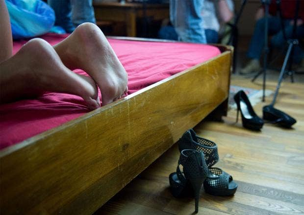 Two porn actresses' shoes lie at the side of a bed Rex