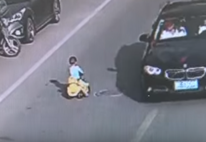 Toddler rides toy vehicle against traffic on busy road