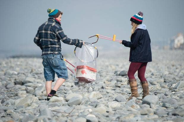 Two young people boy girl Aberystwyth university student volunteers cleaning rubbish off the beach, Borth Ceredigion Wales UK