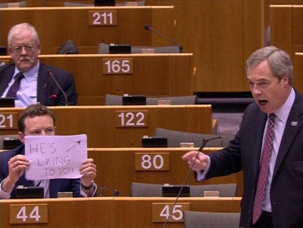 MEP holds sign behind Nigel Farage's head saying 'He's lying to you'