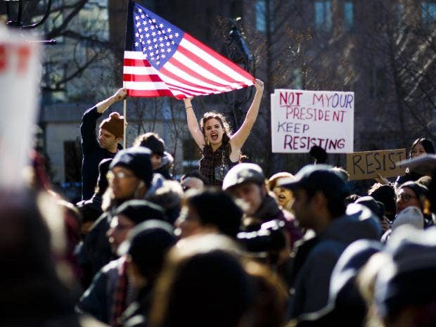 protesters-hold-us-flag-during-a-protest-against-us-president-donald-j.-trump-in-washington-square-park-in-new-york-new-york-usa-17-february-2017.jpg