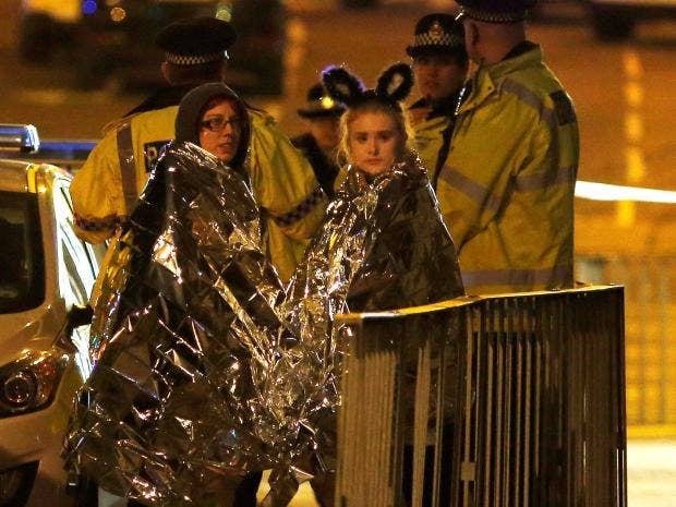 Two women wrapped in thermal blankets stand near the Manchester Arena, where U.S. singer Ariana Grande had been performing