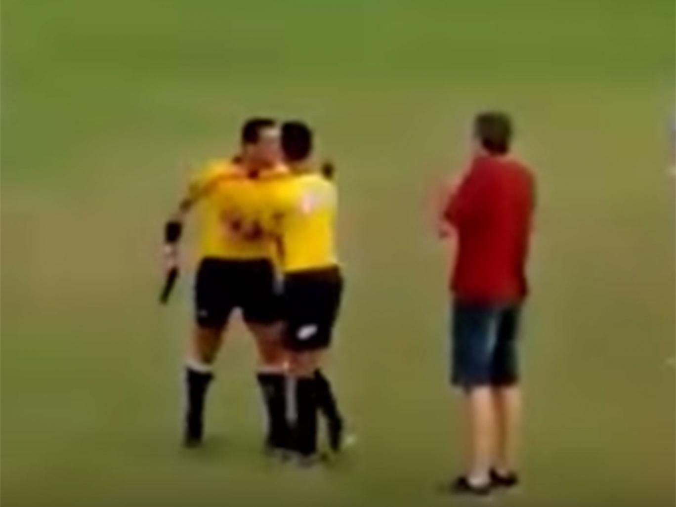 Referee Gabriel Murta pulls a gun during a match
