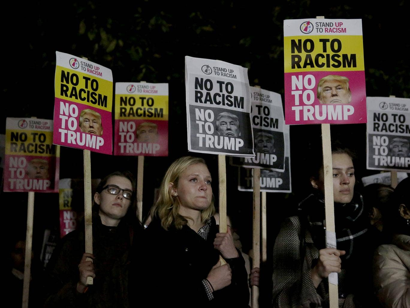 People hold placards as they take part in an anti-racism protest against President-elect Donald Trump winning the American election, outside the U.S. embassy in London