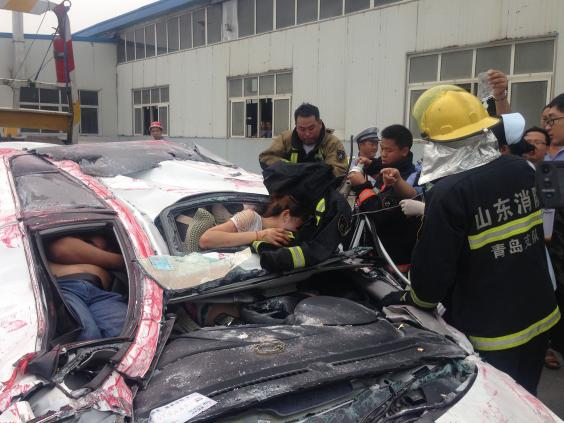 firefighters work to free the woman from the flattened car