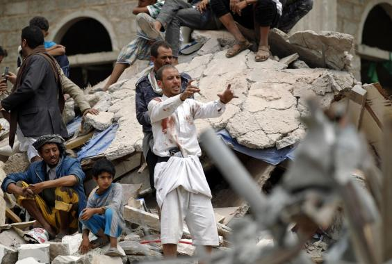 Yemeni man covered in blood stains reacts as rescuers search for survivors in the debris of buildings in Sanaa: AFP/GettyImages