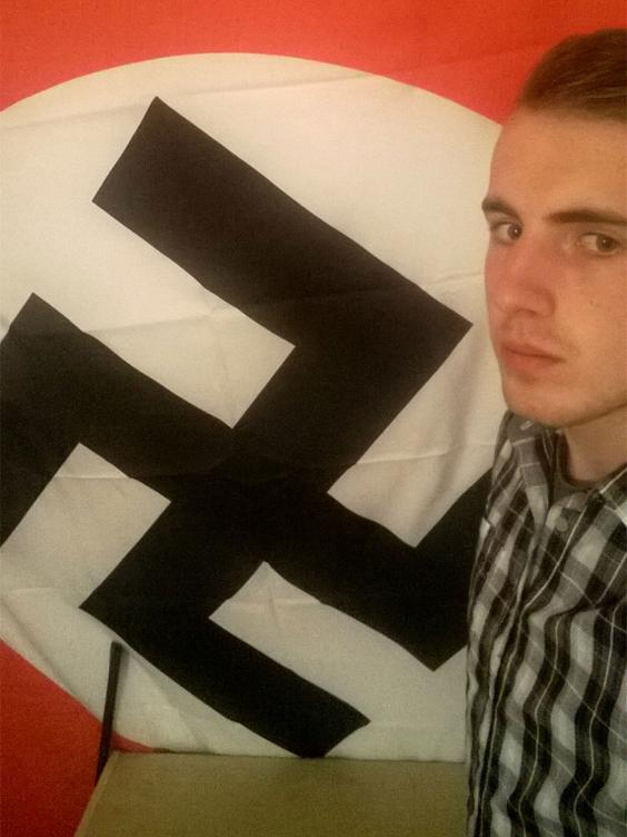 Ethan Stables posing with a Nazi flag at his flat in Barrow, Cumbria (Greater Manchester Police)