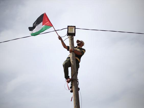 "gaza.jpg ""title ="" gaza.jpg ""/> [19659017] A man hangs a Palestinian flag on an electric pole (REUTERS / <span class="