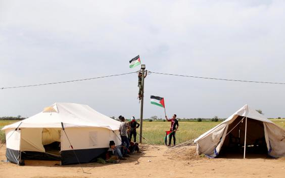 "gaza3.jpg ""title ="" gaza3.jpg ""/> </div> <p><!-- END scald=6159286 --></div> <p>  A man hangs a Palestinian flag amidst a collection of tents near the border with Israel, in the southern Gaza Strip (REUTERS / <span class="