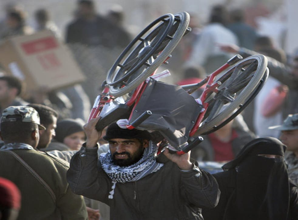 A Palestinian man carries a wheelchair across the boarder back to Gaza