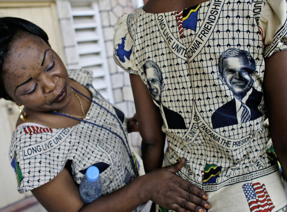 Tanzanian women put the final touches to traditional dresses printed with the portrait of President Bush
