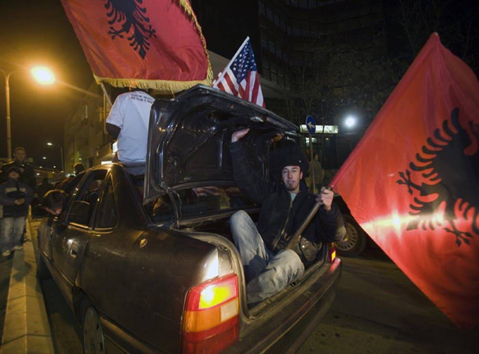 Ethnic Albanians carrying US and Albanian flags celebrate in the center of Kosovo's capital Pristina