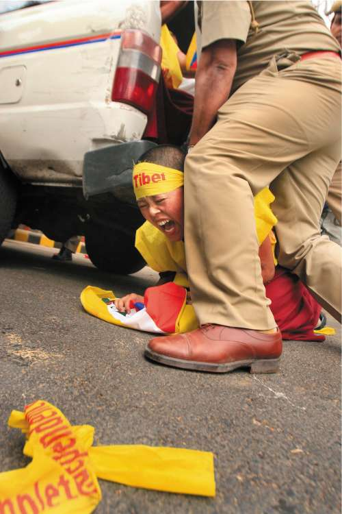 Indian police detain a Tibetan protesting in support of monks inside Tibet