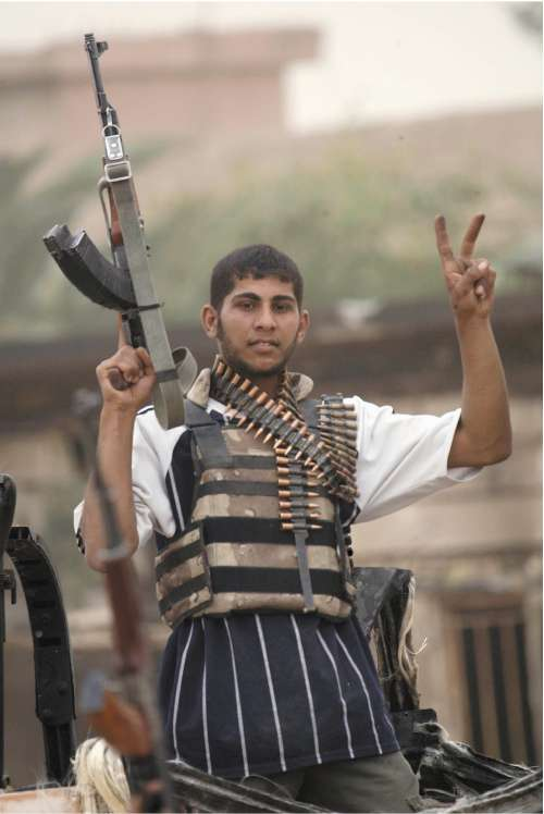 A Mehdi Army fighter flashes a victory sign in Basra yesterday