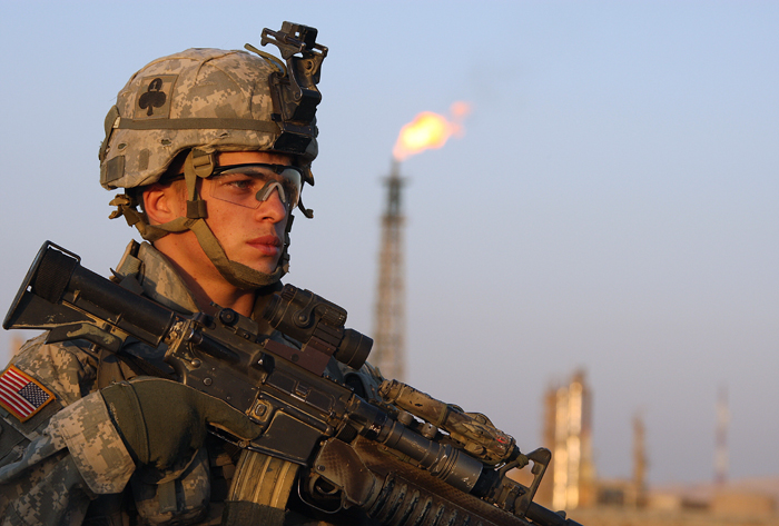 A US soldier stands guard in front of an Iraqi oil refinery near Baiji